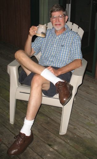 Author Jim Bond, relaxing in an armchair on a porch while drinking tea from his favorite mug